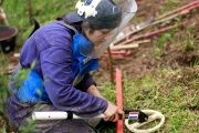 A woman in Colombia practices searching for landmines during a training session.