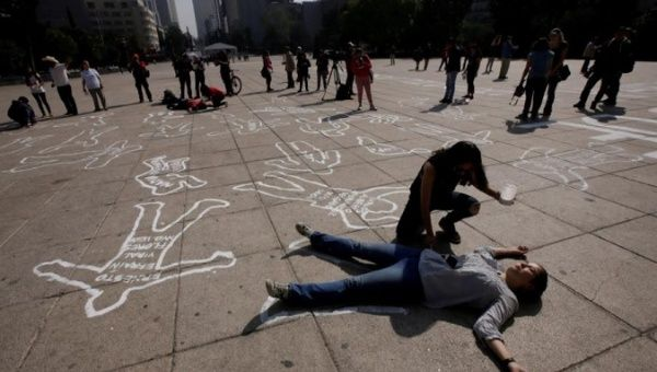 Demonstrators lie on silhouettes that represent victims of violence in Mexico City, December 2016.