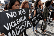 Women attending a protest against femicide in Mexico hold aloft a banner declaring: