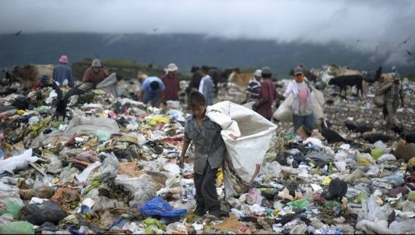 A young boy collects waste at a landfill on the outskirts of Tegucigalpa, Honduras. According to the World Bank, 64.5 percent of the population in Honduras lives in poverty while 42.6 percent live in extreme poverty (less than US$2.50 per day). Photo:Reuters