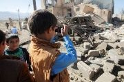 A boy takes a picture of a house laid to rubble by Saudi aerial shelling.