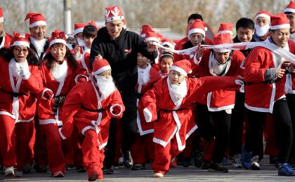 People dressed in Santa Claus costumes during a fun run in the countdown to Christmas Eve in Beijing, China.