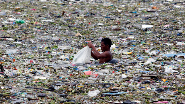 A man collects plastic and other recyclable materials from debris in the waters of Manila Bay in Manila, Philippines, July 30, 2012. Mismanaged waste from land is the primary cause of the ocean plastics crisis.