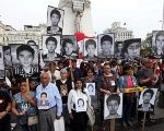 People holding pictures of victims of the conflict in the 1980s and 1990s march after Peruvian President Kuczynski pardoned former President Alberto Fujimori.