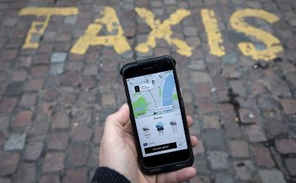 A photo illustration shows the Uber app on a mobile telephone, as it is held up for a posed photograph, in London, Britain Nov. 10, 2017.