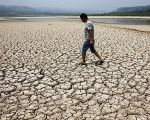 A man walks through the dried-up bed of a reservoir in Sanyuan county, Shaanxi province.