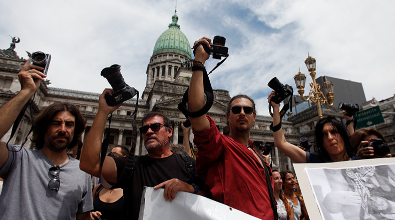 Photographers lift their cameras in front of Argentina