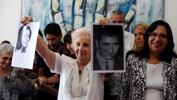 Estela de Carlotto holds pictures of Maria del Carmen Moyano and Carlos Poblete.
