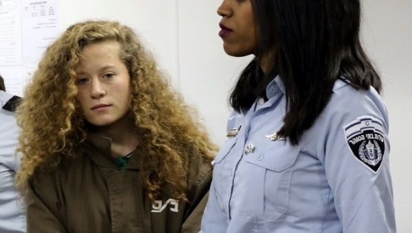 Palestinian teen Ahed Tamimi enters an Israeli courtroom escorted at Ofer Prison near the West Bank city of Ramallah, Dec. 28, 2017.