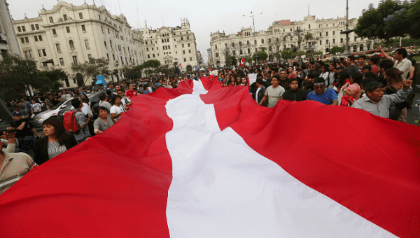 Protesters carry a giant Peruvian flag through the streets of Lima.