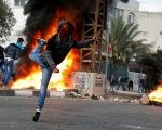 Palestinian demonstrator hurls stones toward Israeli troops during clashes at a protest near the West Bank city of Nablus.