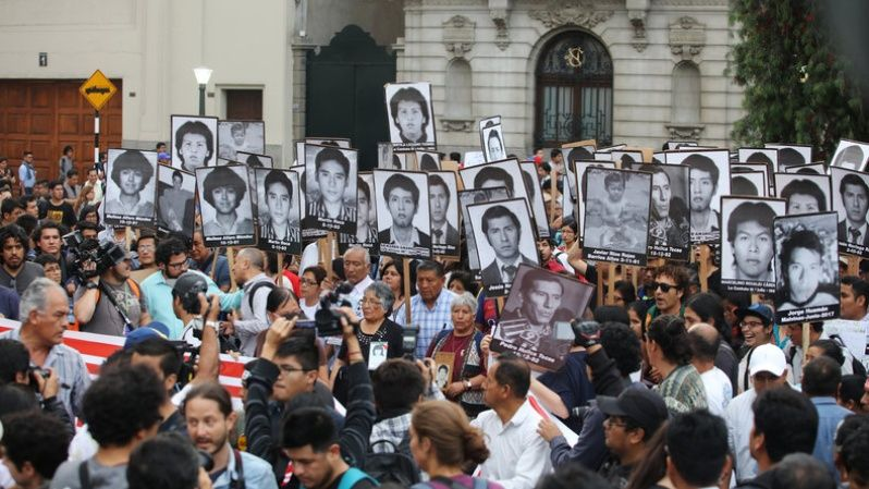 People holding pictures of victims of the guerrilla conflict in the 80s and 90s march against President Pedro Pablo Kuczynski