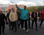 Venezuelan President Nicolas Maduro (C) waves as he arrives for an event to hand over residences built under the government's housing program.