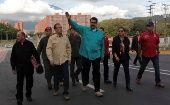 Venezuelan President Nicolas Maduro (C) waves as he arrives for an event to hand over residences built under the government