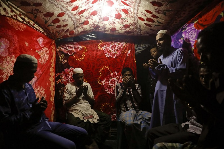 A Muslim cleric (right) officiates the prayers and performs the religious ceremony to marry the couple in a small tent decorated with blankets in vibrant patterns. Only men attend this ceremony.