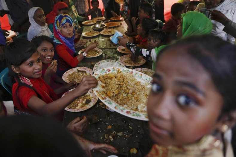 Men are served first, then the women sit down and lastly, the children eat. The free meal is distributed to children in plastic bags, but a scuffle that erupts means that some of it ends up in the mud.