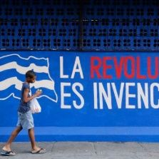 "A boy walks past a graffiti reading ""The revolution is invincible"" in Havana December 23, 2014."