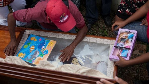 Alexander Conopoy reacts over the coffin of his daughter Alexandra Conopoy, a pregnant 18 year-old killed in Charallave, Venezuela Jan. 1, 2018.