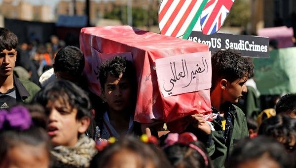 Children carry a mock coffin during a protest against the Saudi-led coalition outside the UN offices in Sanaa, Yemen Nov. 20, 2017.