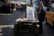 A Palestinian man stands next to a cart carrying a flour sack distributed by UNRWA in Khan Younis refugee camp in the southern Gaza Strip Jan. 3, 2018.