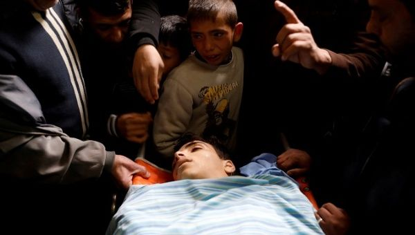 People gather around the body of Mosab Tamimi, who was killed during clashes with Israeli troops, at a hospital in the West Bank city of Ramallah Jan. 3, 2018.