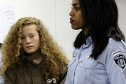 Palestinian teen Ahed Tamimi enters a military courtroom escorted by Israeli Prison Service personnel at Ofer Prison near the West Bank city of Ramallah, December 28, 2017.