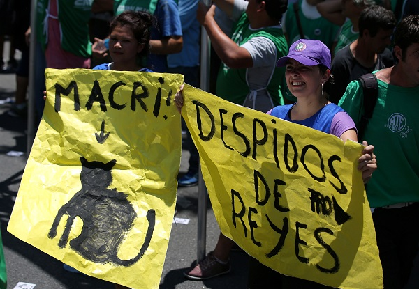 A woman holds a banner that reads in Spanish,