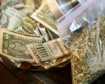 A bag of marijuana being prepared for sale sits next to a money jar at BotanaCare in Northglenn, Colorado, U.S., Dec. 31, 2013.