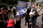 An opposition supporter holds up the Constitution of the Republic of Honduras during a protest over a contested presidential election with allegations of electoral fraud in Honduras.