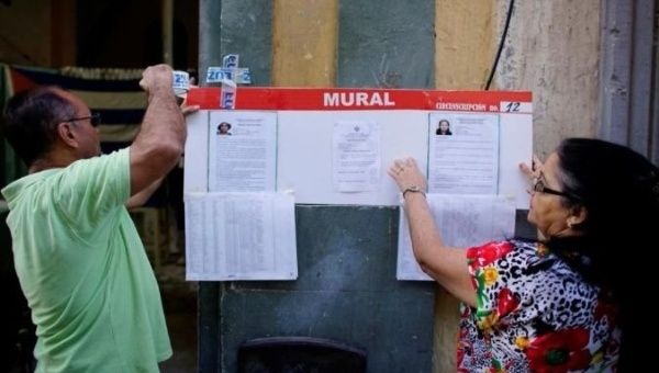 Election officials hang pictures and CVs of municipal assembly candidates moments before opening a polling station in Havana, Cuba on Nov. 26, 2017.