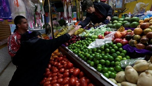 A woman buys vegetables at a market stall in Mexico City, January 2018.