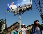 Locals walk past a banner of Pope Francis ahead of the papal visit, in Temuco, Chile Jan. 10, 2018.