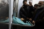 People stand next to the body of Palestinian boy Ameer Abu Mosaed, at a hospital morgue in the central Gaza Strip Jan. 11, 2018.
