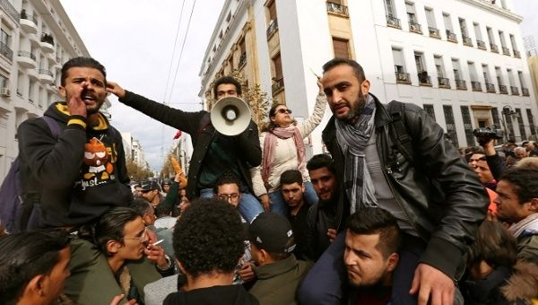 Demonstrating graduate students shout slogans, as riot police stand guard, during protests against rising prices and tax increases, in Tunis, Tunisia January 12, 2018.