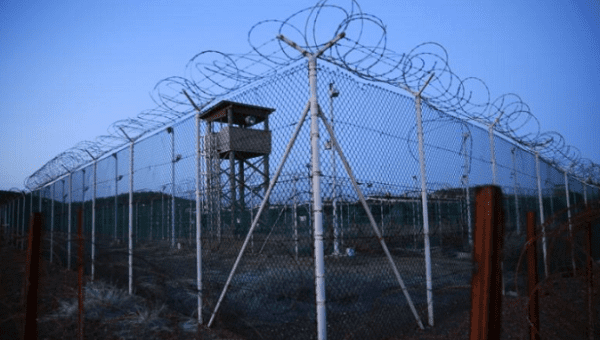 Chain link fence and concertina wire surrounds a deserted guard tower within Joint Task Force Guantanamo