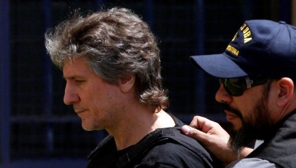 Former Argentine Vice President Amado Boudou is escorted by a member of Argentina