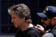 Former Argentine Vice President Amado Boudou is escorted by a member of Argentina's Coastguards as he arrives at a Federal Justice building in Buenos Aires.