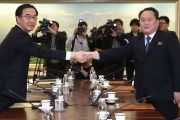 Ri Son-gwon (right), head of the North Korean delegation, shakes hands with his South Korean counterpart Cho Myoung-gyon during their meeting at the truce village of Panmunjom on Tuesday.