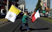 Chilean and Vatican flags are carried by a man ahead of the papal visit in Temuco, Chile.