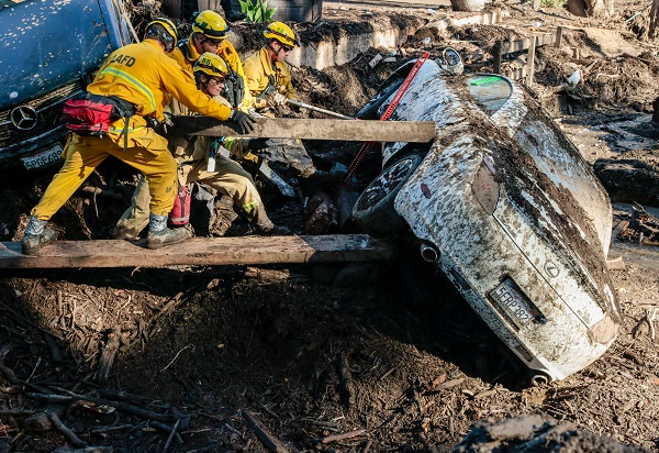 Excavators carrying rescuers in their buckets plowed through mud-coated roads in search of the missing after some areas were buried in as much as 4.6 meters of mud, emergency officials said.