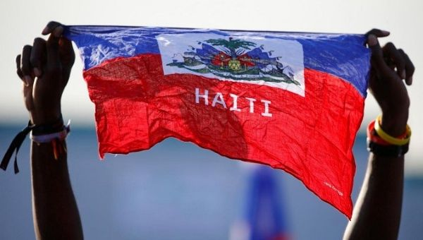A girl holds national flag of Haiti before Pope Francis