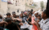 People gather to collect food rations at a food distribution center in Sanaa, Yemen on March 21, 2017.