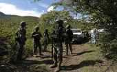 Soldiers guard an area where a mass grave was found, in Colonia las Parotas on the outskirts of Iguala, in Guerrero in October 2014.