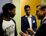 French President Emmanuel Macron (R) talks to Ahmed Adam from Sudan at a migrant center in Croisilles, France, January 16.