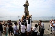 Religious group and non-government organizations offer flowers at a memorial statue that commemorates the Filipino