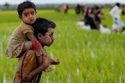 A Rohingya boy carries a child after after crossing the Bangladesh-Myanmar border in Teknaf, Bangladesh.