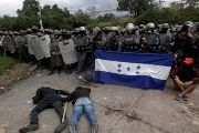 Opposition supporters hold a Honduran flag as others lie on the floor in front of security forces during post-electoral protest.