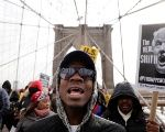 Demonstrators protesting against US President Donald Trump's recent statements about immigration and Haiti march over the Brooklyn Bridge in New York.
