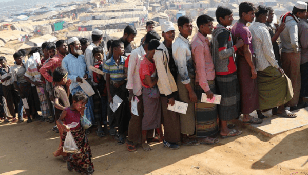 Rohingya refugees stand in a queue to collect aid supplies in Kutupalong refugee camp in Cox
