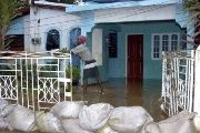 A man drains water from his house flooded after the passage of Hurricane Dennis in the city of Kigston, Jamaica